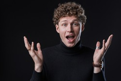 Excited young man wearing turtleneck standing isolated infront of a black background, looking at camera