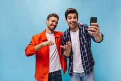 Excited young men in white t-shirts and jeans smile sincerely and talk by video link on phone. Guy in checkered shirt holds smartphone on blue background.