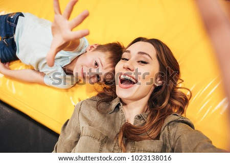 Excited young mother playing with her little son at the entertainment centre together and taking a selfie #1023138016