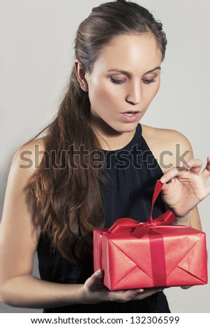 Excited young pretty woman open christmas gift or birthday present. Gray background. Copyspace.