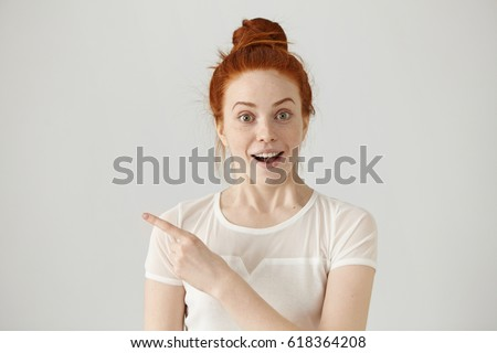 Excited young redhead Caucasian woman with hair knot pointing her index finger sideways, raising eyebrows and keeping mouth wide opened, showing something surprising on grey copy space wall #618364208