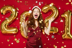 Excited young redhead Santa woman in elegant dress Christmas hat hold champagne isolated on red background confetti golden numbers air balloons. Happy New Year 2021 celebration holiday party concept