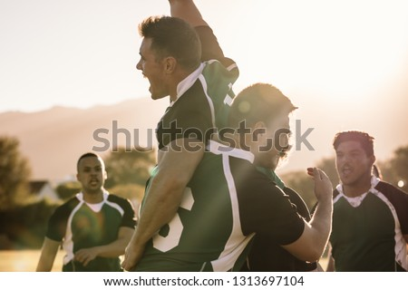 Excited young rugby players celebrating a win at the sports field. Rugby team enjoying after the victory.
