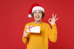 Excited young Santa woman in casual yellow sweater Christmas hat hold gift certificate showing OK gesture isolated on red background studio portrait. Happy New Year celebration merry holiday concept