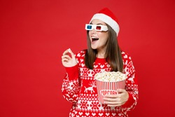 Excited young Santa woman in sweater Christmas hat 3d glasses watching movie film hold bucket of popcorn isolated on red background studio portrait. Happy New Year celebration merry holiday concept