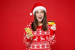 Excited young Santa woman 20s in sweater, Christmas hat using mobile cell phone hold credit bank card isolated on red background, studio portrait. Happy New Year celebration merry holiday concept