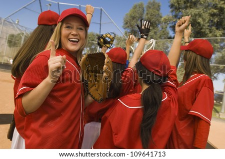 Excited young softball player with team after a winning game