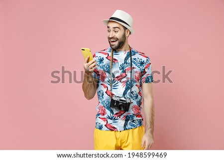 Excited young traveler tourist man in summer clothes, hat using mobile cell phone typing sms message isolated on pink background. Passenger traveling abroad on weekends. Air flight journey concept