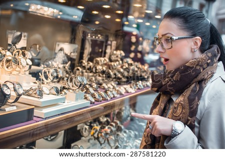 Excited young woman looking to showcase or shop window. Shopping girl chooses jewelry in store