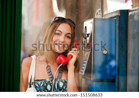 Excited young woman making a phone call in telephone box