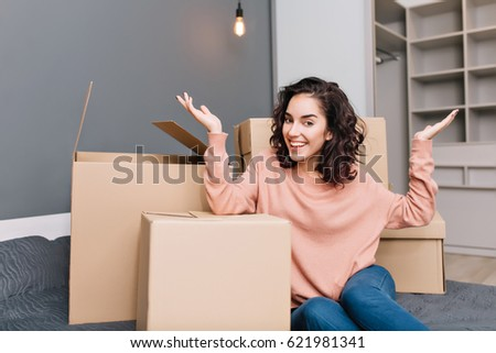 Excited young woman on bed suround boxes, carton smiling to camera in modern apartment. Moving to new flat, expressing true positive emotions at new home with modern interior