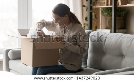 Excited young woman sit on couch in living room hold cardboard box unpacking delivered package, happy millennial girl in glasses open carton parcel at home unboxing goods shopping online