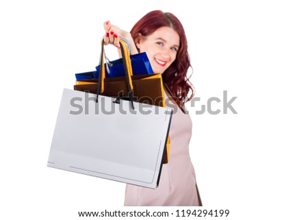 Excited young woman smiling with hand stretched forward holding paper shopping bags isolated over white background.