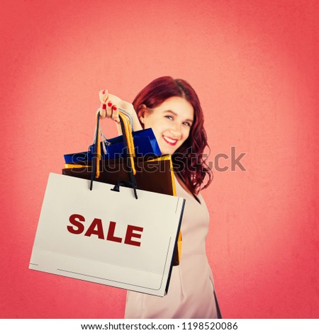Excited young woman smiling with hand stretched forward holding paper shopping bags isolated over red background. Sale for christmas holiday.