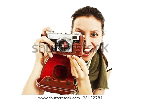 Excited young woman taking a picture with an old camera against white background