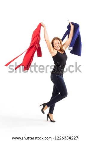 excited young woman triumphantly holds the clothes in her hands. the concept of successful shopping. isolated on white background. vertical