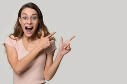 Excited young woman wearing glasses pointing fingers at copy space, surprised female with open mouth looking at camera, satisfied client customer showing offer, isolated on studio background