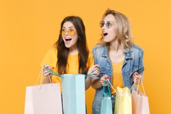 Excited young women girls friends in denim clothes eyeglasses posing isolated on yellow background in studio. People lifestyle concept. Hold package bag with purchases after shopping, looking aside