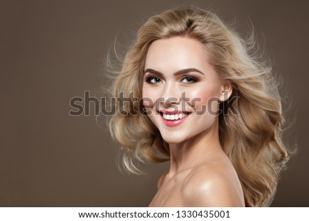 Excitement Blonde haired Woman Portrait with blue eyes and Healthy Long Shiny Wavy hairstyle. Volume shampoo. Blond Curly permed Hair and bright makeup.   #1330435001