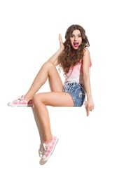 Excitement on a Banner. Shocked sexy woman in pink top, jeans shorts and pink sneakers sitting on the white banner and pointing down. Full length studio shot isolated on white.
