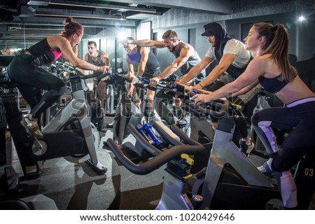 Excitement sporty people working out on cycling class at gym.