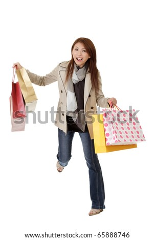 Exciting shopping woman of Asian holding bags isolated over white.