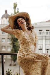 Exciting woman in stylish flower clothes laughing on terrace. Gorgeous girl with wavy hair in earrings and hat smiling on balcony..