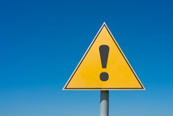 Exclamation mark on a yellow road sign. Against the blue sky Warning, danger, attention