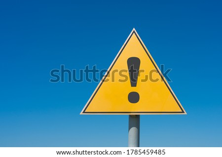 Photo of  Exclamation mark on a yellow road sign. Against the blue sky Warning, danger, attention