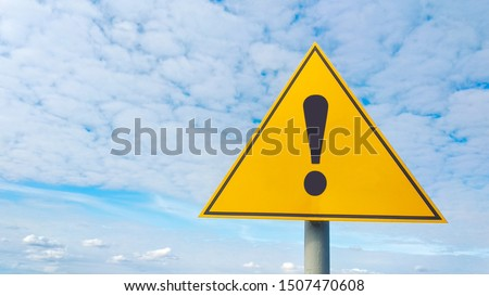 Exclamation point of attention against the sky. yellow triangular sign. Danger warning. Attention