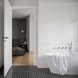 Exclusive bathroom with modern floor tiles and elegant bathtub next to bedroom with big and comfortable bed