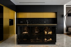 Exclusive kitchen with gold and black furniture, big kitchen island and elegant marble floor tiles