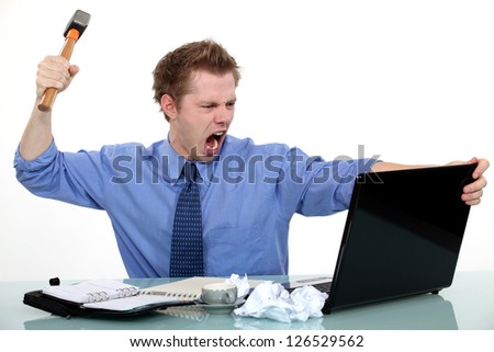 Executive about to smash his laptop with a hammer.