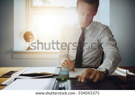 Executive business man working on accounts while being concentrated and serious, wearing white shirt and tie