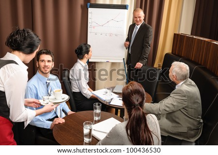 Executive businessman giving presentation on flip-chart to team formal-wear