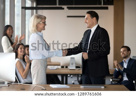 Executive ceo manager and middle aged female employee shake hands congratulating with promotion, rewarding praising motivating appreciating good result, respect feedback concept recognition handshake #1289761606