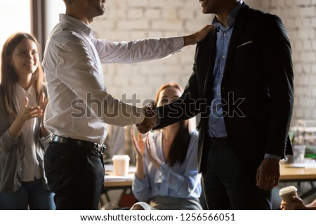 Executive director manager handshaking worker promoting motivating employee shake hands promise rewarding thanking for good work, feedback respect, rewarding recognition concept, team support applaud