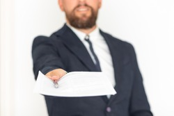 Executive hand with blue suit and beard handing over contract and pen