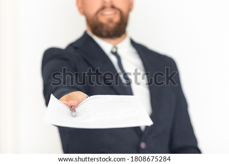 Executive hand with blue suit and beard handing over contract and pen Foto stock ©