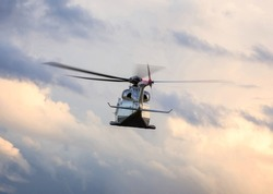 Executive heavy class helicopter shot in flight. Motion blurred rotor blades. Evening twilight cloudy sky.