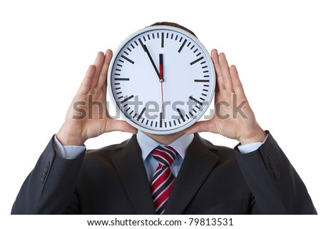 Executive holds clock in front of face as a sign of overload.Isolated on white background.