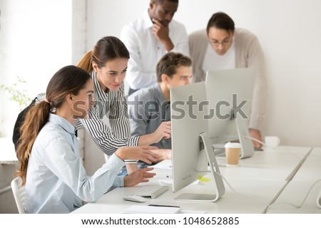 Executive mentor explaining intern or new employee online task pointing at computer screen, female boss supervisor teaching young girl to use corporate software or helping with difficult assignment Foto stock ©