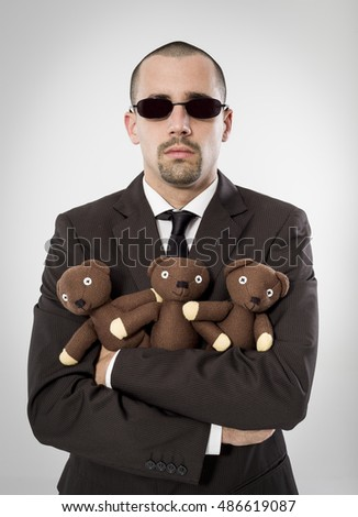 Executive portrait hugging a teddy bears on neutral background