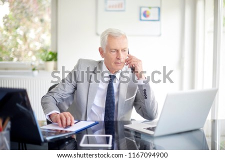 Executive senior businessman using his mobile phone and talking wih somebody while working laptop in the office.