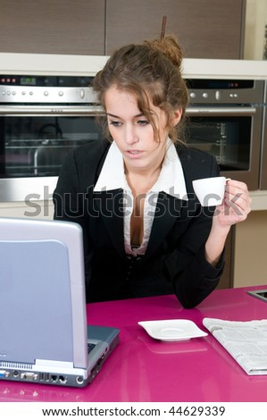 executive woman in kitchen with coffee looking at laptop computer