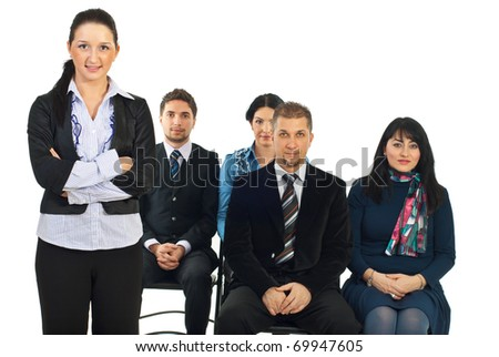 Executive woman standing with arms folded in front of classroom with business people sitting on chairs over white background - stock photo
