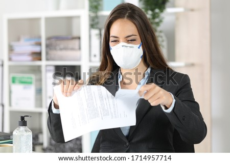 Executive woman wearing protective mask ripping contract on a desk at the office Foto d'archivio ©