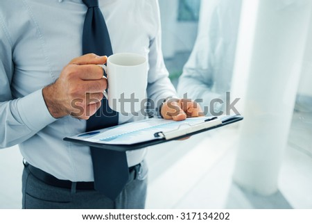 Executive working during his coffee break, he is holding a clipboard and a mug with coffee