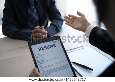 Executives are interviewing candidates and holding a tablet, opening the resume from the email that the applicant submits online. Discussing attitudes about work and special abilities. Considerations. #1422848717