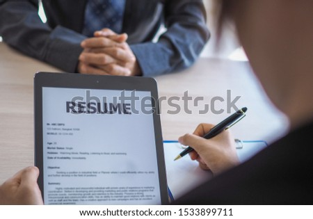 Executives are interviewing candidates and holding a tablet, opening the resume from the email that the applicant submits online. Discussing attitudes about work and special abilities. Considerations